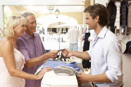 Male Sales Assistant At Checkout Of Clothing Store With Customer